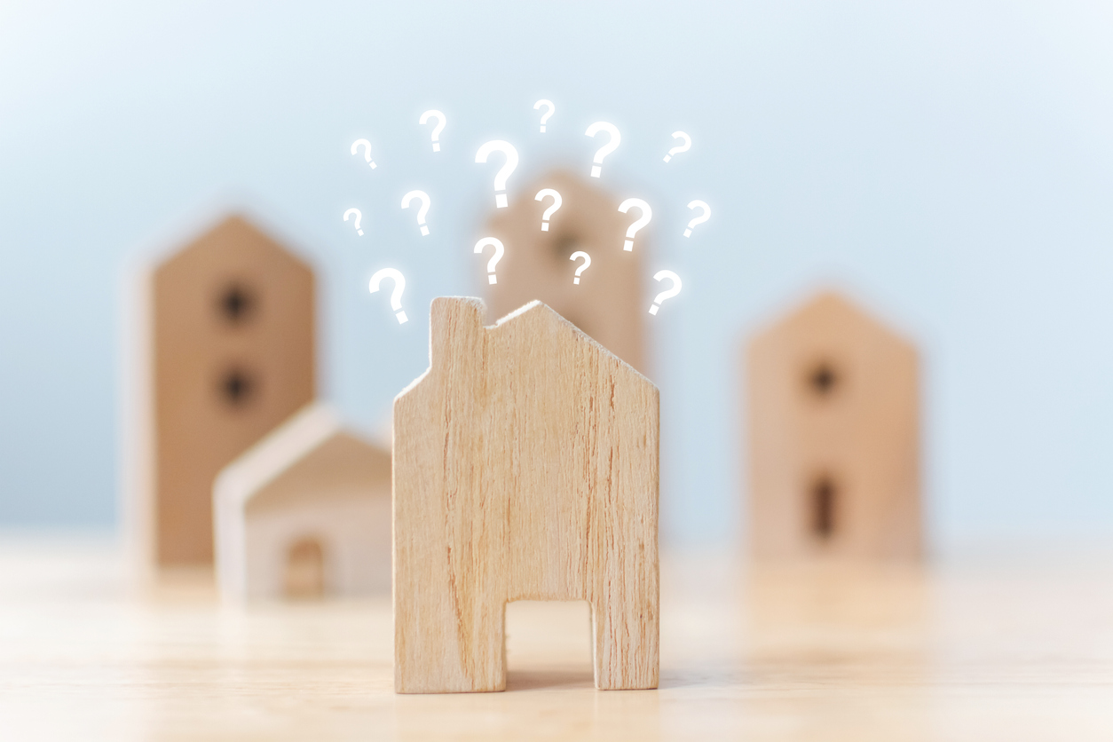 wooden cut-out house with question marks