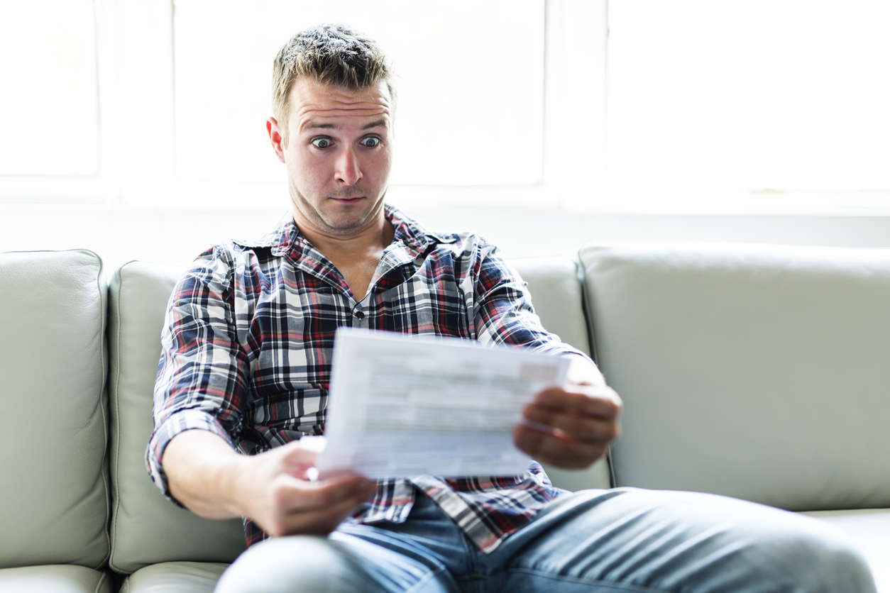 shocked person sitting on a sofa looking at a large bill